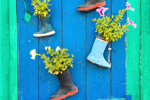 Stare dziecięce kalosze z kwitnącymi letnimi kwiatami na drzwiach wejściowych domu