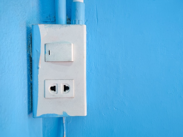 Stare gniazdka i przełączniki są zamontowane na niebieskich cementowych ścianach wewnątrz budynku.