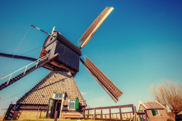 Stare holenderskie wiatraki wyskakują z kanału w rotterdamie. holandia.