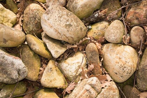 Stare i brudne okrągłe kamienie peeble i liść