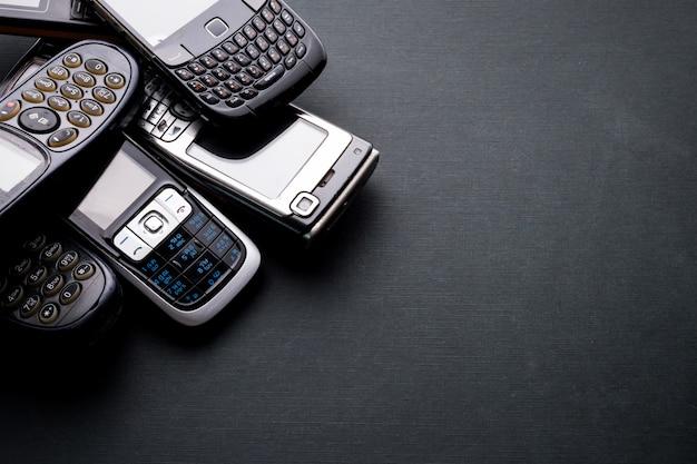 Stare i przestarzałe telefony komórkowe na czarnym tle.