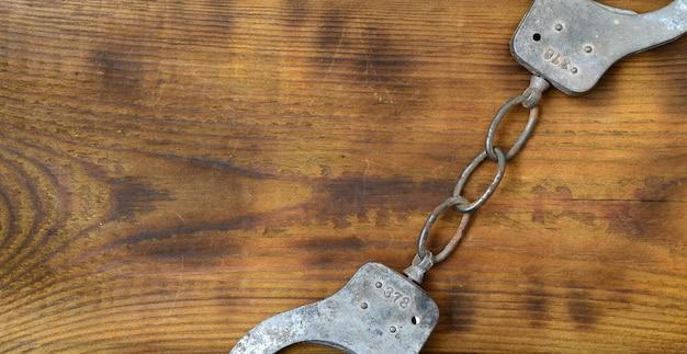 Stare i zardzewiałe kajdanki policyjne leżą na porysowanej powierzchni drewnianej. pojęcie starej zbrodni
