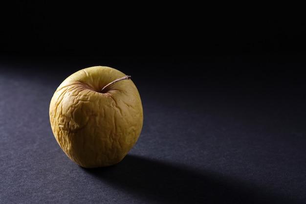 Stare jabłko zaczyna gnić na czarnym tle