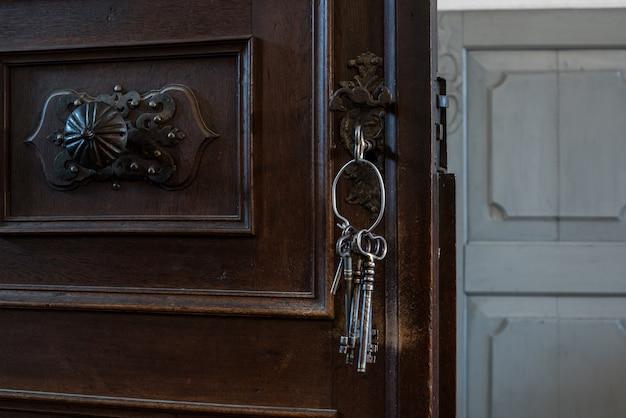 Stare klucze w dziurce od klucza. stary zardzewiały drewniane drzwi z kluczami.