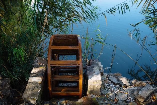 Stare koło wodne znajduje się na jeziorze otoczonym drzewami i skałami