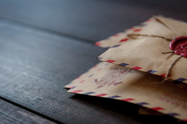 Stare koperty vintage retro z woskową pieczęcią na starym ciemnym brązowym drewnianym stole