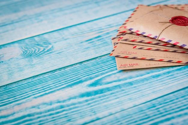 Stare koperty vintage retro z woskową pieczęcią na starym niebieskim drewnianym stole