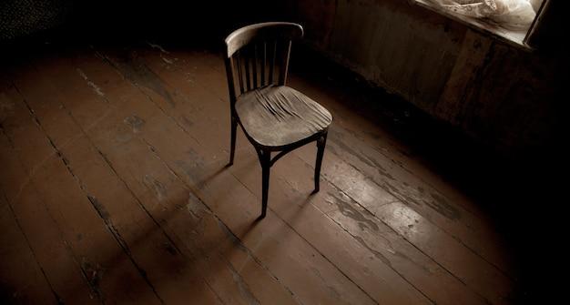 Stare krzesło w starym i ciemnym pokoju