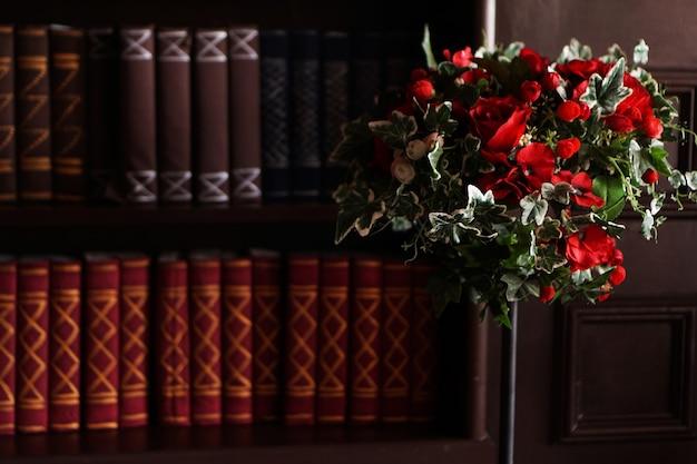 Stare książki na archiwalnej półce biblioteki magazynu. dwa rzędy książek i czerwone kwiaty