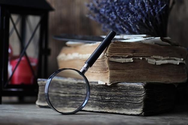 Stare książki na drewnianym stole i szklanej lupie