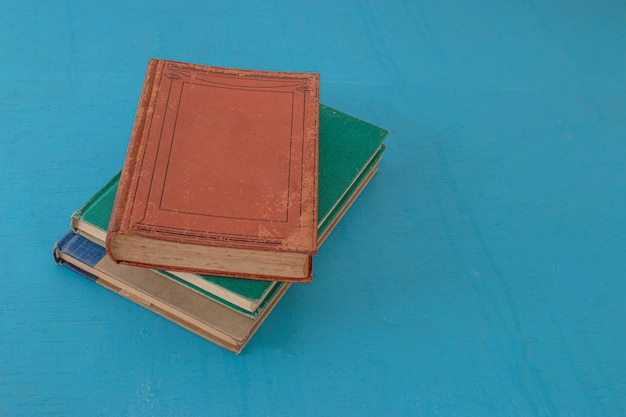 Stare książki na niebiesko-zielonym drewnianym. widok z góry.