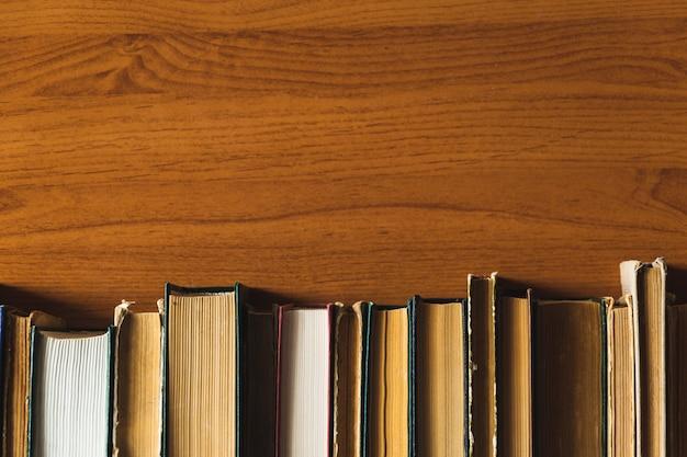 Stare książki na półce z drewnianymi