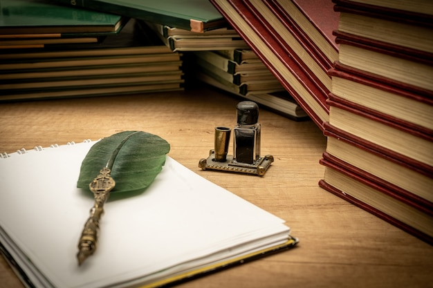 Stare książki ułożone w nieładzie, stary długopis z atramentem i notatnik na starym drewnianym stole