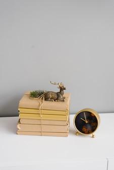 Stare książki w beżowej okładce z papieru, na której stoi statuetka siedzącego jelenia