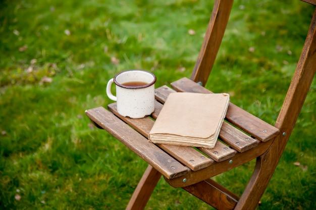 Stare książki z filiżanką herbaty na stole na zielonej trawie na wiosnę