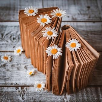 Stare książki z kwiatami białych stokrotek polnych.