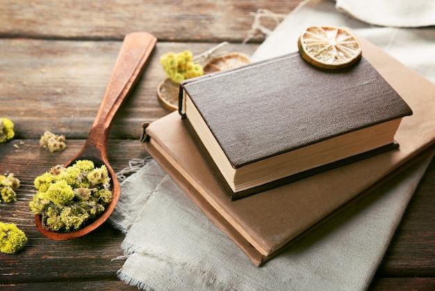 Stare książki z suchymi kwiatami i cytryną na stole z bliska