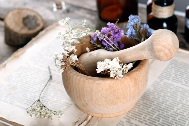 Stare książki z suchymi kwiatami w moździerzu i butelkach na stole z bliska