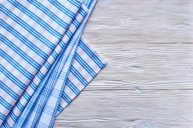 Stare lekkie drewniane tła. drewniany stół z niebiesko-białym ręcznikiem kuchennym