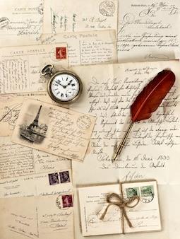 Stare listy i pocztówki z piórkiem i zabytkowym zegarem. nostalgiczne tło