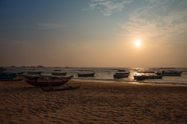 Stare łodzie na oceanie o zachodzie słońca