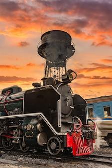 Stare lokomotywy parowe na tle zachodu słońca.