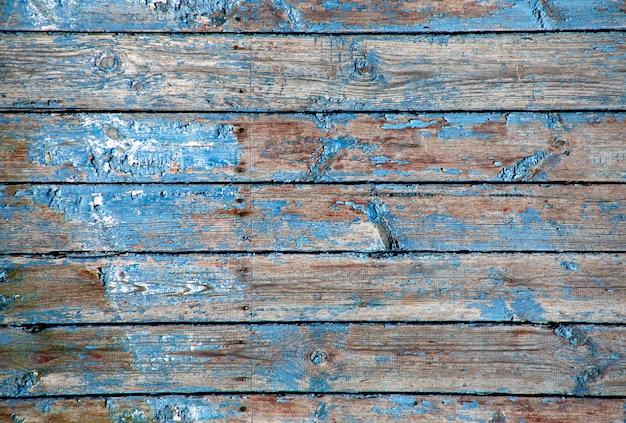 Stare łuszczenie niebieskiej farby na drewnianej teksturze.