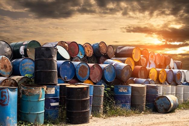 Stare metalowe zbiorniki chemiczne o zachodzie słońca, brudne bębny ze stali olejowej, środowisko, usuwanie substancji chemicznych