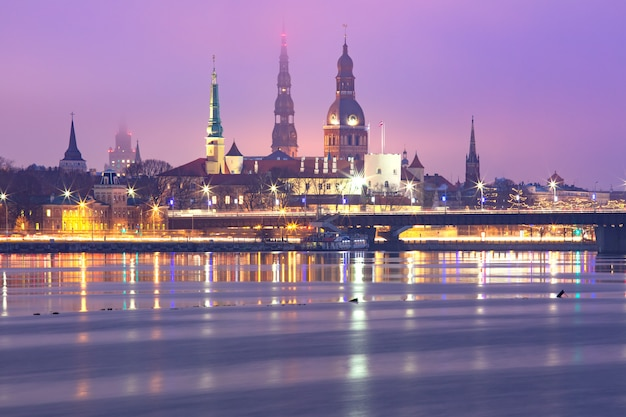 Stare miasto i rzeka daugava w nocy, ryga, łotwa