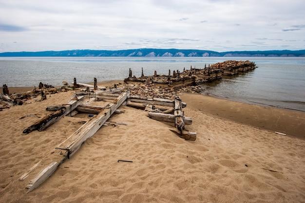 Stare molo zepsute łodzie na wyspie olkhon na jeziorze bajkał. zgniłe pręty i kłody. na brzegu kamieni i piasku. za górskim jeziorem. pogoda jest ponura, niebo szare.