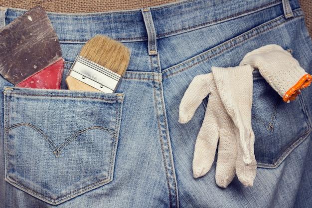 Stare narzędzia do naprawy domu w kieszeniach dżinsów.