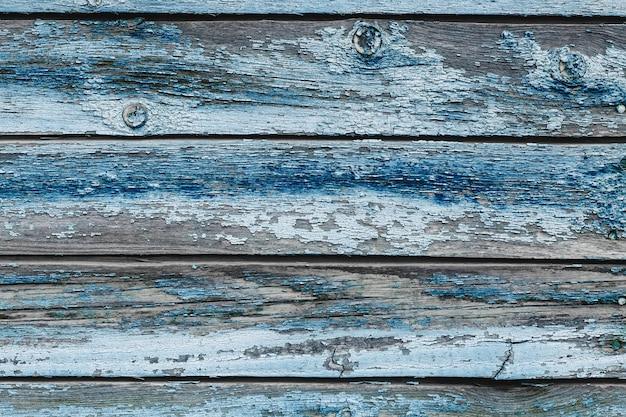 Stare niebieskie wytarte drewniane deski z popękaną farbą
