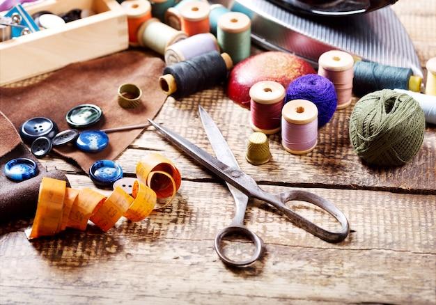 Stare nożyczki, różne nici i narzędzia do szycia na drewnianym stole