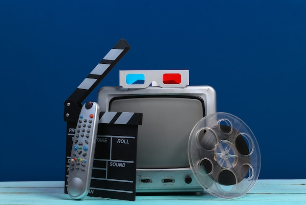 Stare odbiorniki telewizyjne z klapką filmową, rolką filmu, okularami 3d na klasycznym niebieskim. przemysł rozrywkowy, media, produkcja filmowa