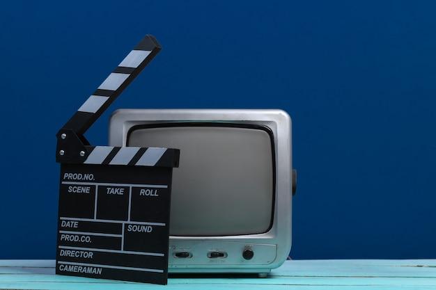 Stare odbiorniki telewizyjne z klapsem filmowym na klasycznym błękicie. przemysł rozrywkowy, media