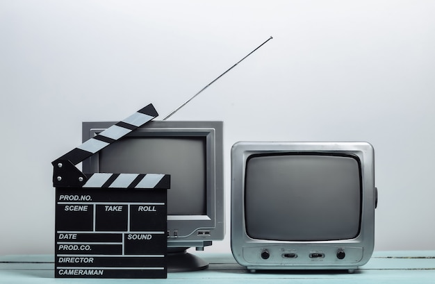Stare odbiorniki telewizyjne z klapsem filmu na białej ścianie. przemysł rozrywkowy, media