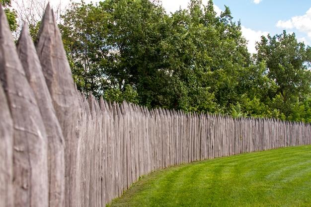 Stare ogrodzenie z palików i konstrukcji ochronnej w pobliżu starej drewnianej fortecy