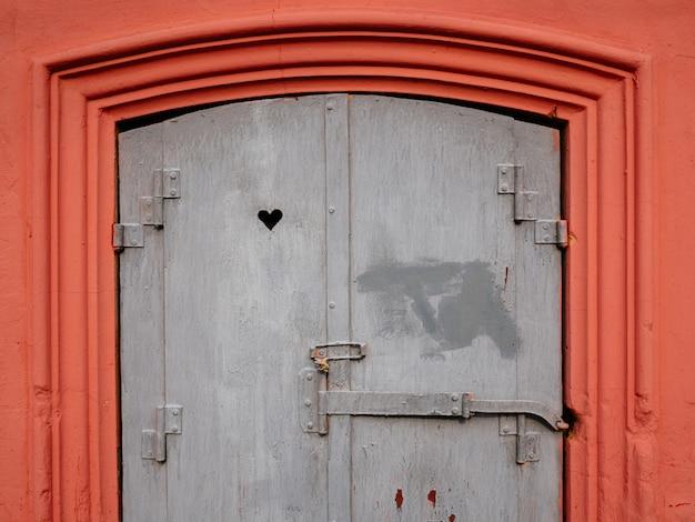Stare okno jest różowe z wzorami. w oknie wyryte jest serce