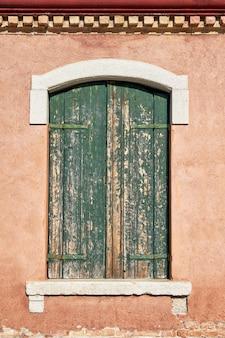 Stare okno z zamkniętą zieloną żaluzją. włochy, wenecja, wyspa burano.