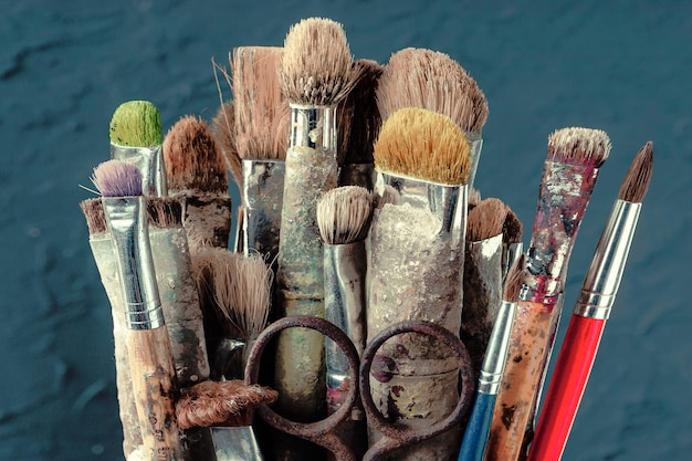 Stare pędzle artystyczne stoją na niebieskiej ścianie kolorowej ściany w pracowni artysty