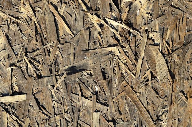 Stare płyty osb są wykonane z brązowych wiórów szlifowanych w drewnianym tle. widok z góry na tło płyty wiórowej fornirowanej osb, ciasne, bezszwowe powierzchnie