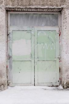 Stare pomalowane na zielono zamknięte drzwi. przedni widok. pionowy.