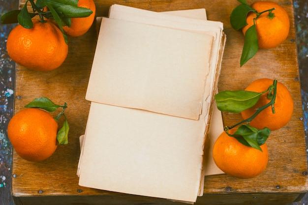 Stare puste arkusze papieru i drewniany stół mandarynki widok z góry