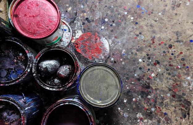 Stare puszki farby z plamami koloru na posadzce cementowej. nad światłem