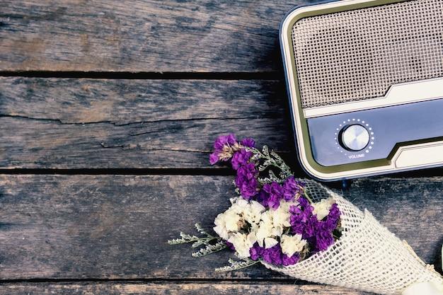 Stare radio retro jest połączone z suszonymi kwiatami na starej drewnianej podłodze