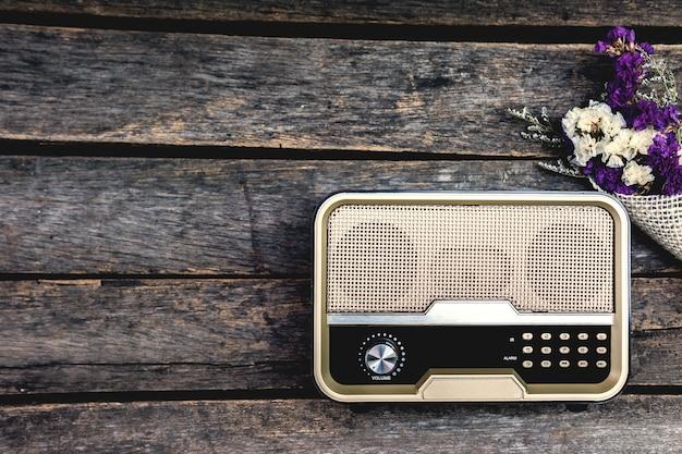 Stare radio w stylu retro jest połączone z suszonymi kwiatami na starym drewnianym