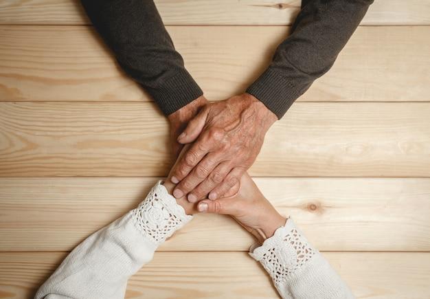Stare ręce starszej pary razem, trzymając się za ręce