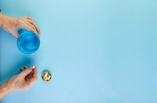 Stare ręce z pigułkami i szklanką wody.