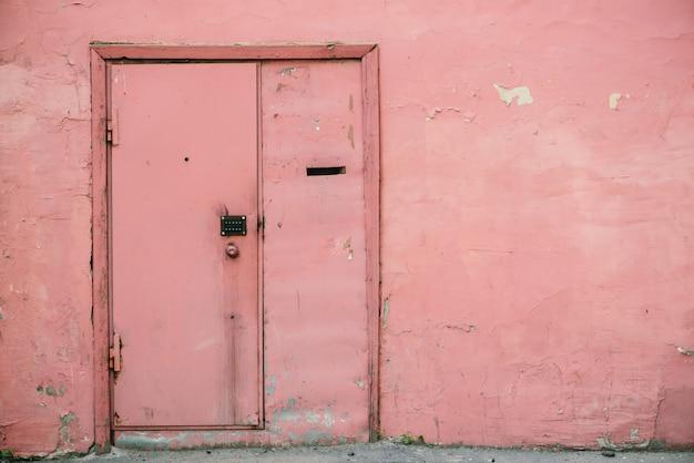 Stare różowe drzwi z zamkiem szyfrowym na unikalnej łuszczącej się ścianie starzejącego się budynku. retro tło wejście w rocznika domu. niezwykła niedoskonała szorstka konstrukcja. dom mieszkalny grunge glamour.