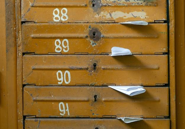 Stare skrzynki pocztowe w holu domu mieszkalnego wypełnione białymi ulotkami